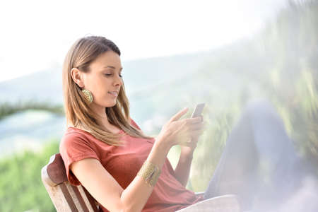 lawn chair: Beautiful woman in lawn chair using smartphone