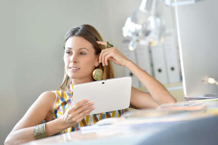 officeworker: Woman in office using digital tablet