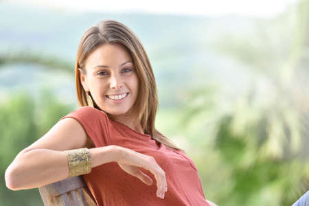 魅力的な若い女性の屋外の椅子でリラックス
