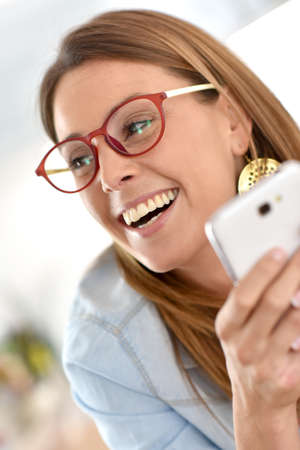 optical: Cheerful girl having fun using smartphone Stock Photo