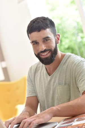 persona feliz: Hombre en el hogar conectado en el ordenador portátil