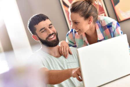 persona feliz: Pareja en casa mirando el sitio web de la decoración en la computadora portátil