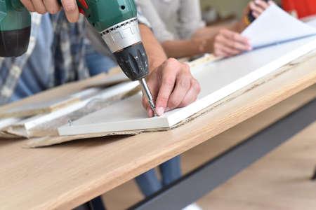 Closeup of electric drill assembling furniture pieces