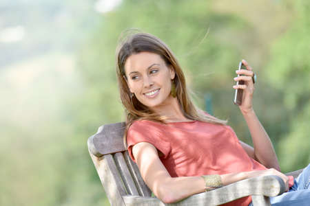 outdoor chair: Beautiful woman in outdoor chair using smartphone Stock Photo