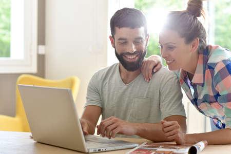 pareja en casa: Pareja en casa mirando el sitio web de la decoración en la computadora portátil