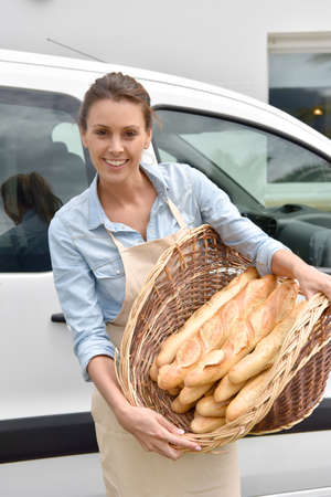 delivering: Cheerful baker delivering bread to client