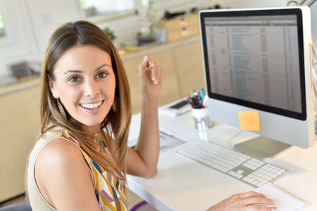 officeworker: Beautiful office worker sitting in front of desktop