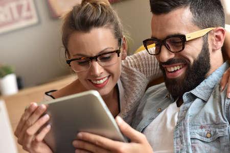 流行に敏感なカップルを持つデジタル タブレットを使用して楽しい
