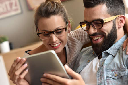 Hipster couple having fun using digital tablet