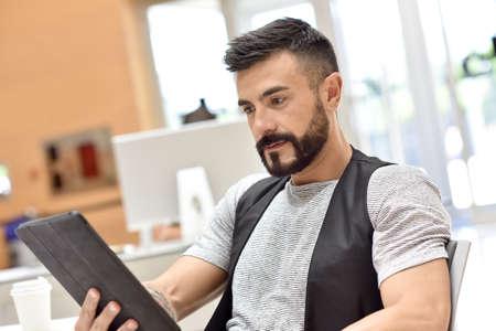 websurfing: Trendy bearded guy in office websurfing on tablet Stock Photo