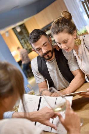 choosing: Young trendy people in restaurant looking at menu