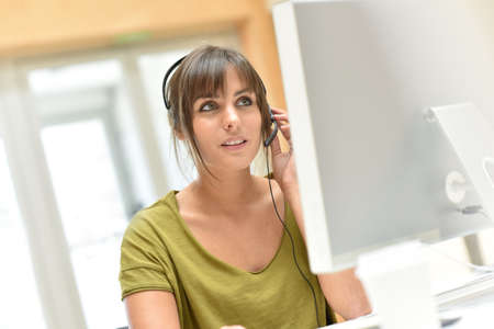 sales representative: Attractive young sales representative with headset Stock Photo