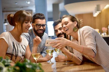 grupos de personas: Grupo de amigos que toman fotos en la barra de autofotos