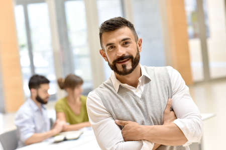Confident man in meeting room, people in background