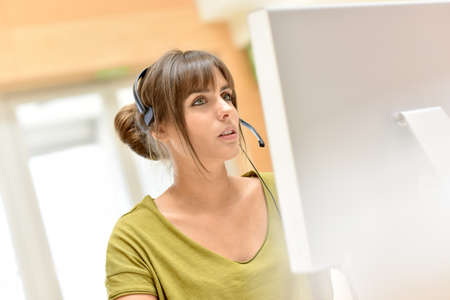 teleoperator: Attractive young sales representative with headset Stock Photo