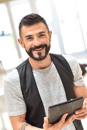 websurfing: Trendy guy in office websurfing on tablet Stock Photo