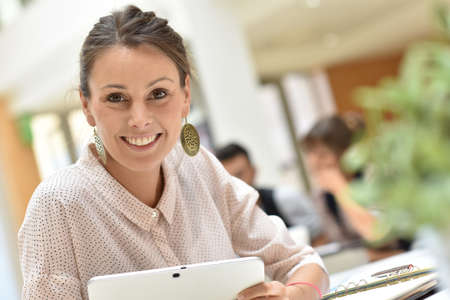 people relaxing: Attractive businesswoman in office working on tablet