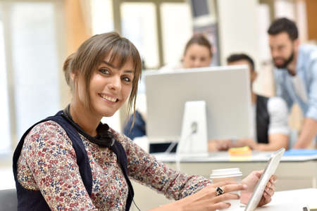officeworker: Trendy young woman in office working on tablet