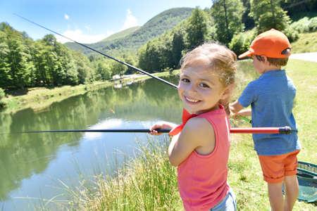 山の湖で釣り少女の肖像画 写真素材