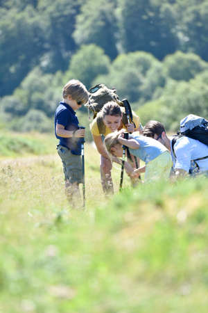Family on a hiking day looking at vegetation Stock Photo