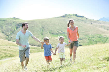 dia soleado: Familia de vacaciones corriendo por la colina