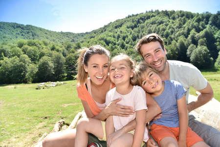 田舎で座っている陽気な家族