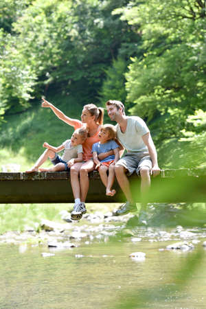 Familie zittend op een brug over bergrivier Stockfoto