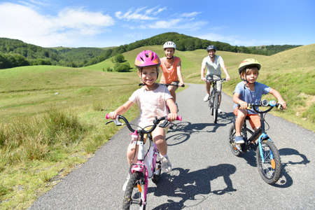 Happy family riding bikes in mountain road Stock Photo