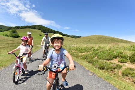 Happy family riding bikes in mountain road Stock Photo
