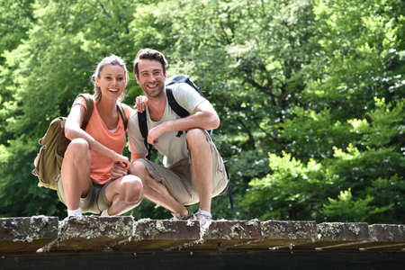 knelt: Couple of hikers knelt on a bridge looking at river water