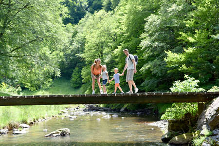 Family of four walking on a bridge crossing the river Banque d'images