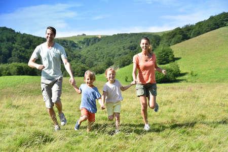 Familia de vacaciones corriendo por la colina
