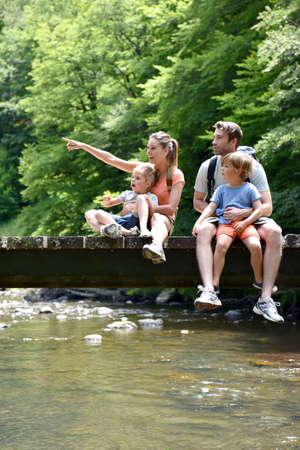 Family sitting on a bridge crossing mountain river Stock Photo