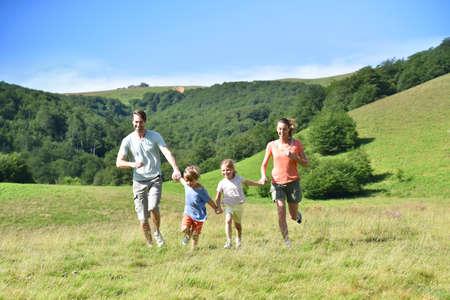 Familie auf Ferien laufen den Berg hinunter