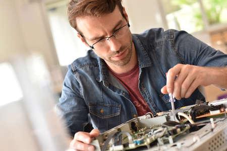 fixing: Repairman fixing tv set