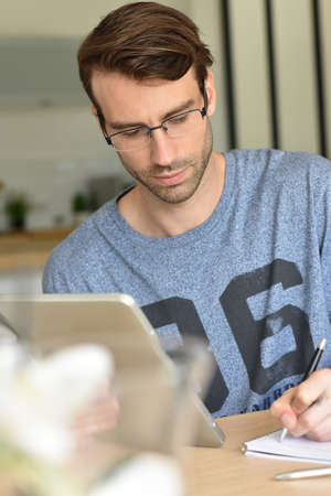 homeoffice: man at home working on digital tablet Stock Photo