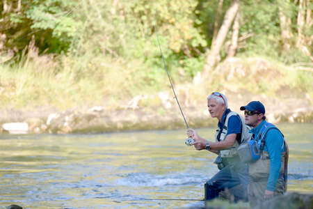 guide: Flyfisherman with fishing guide in river Stock Photo