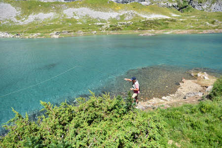 Upper view of flyfisherman fishing in mountain lake