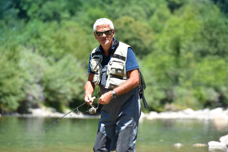waders: Fisherman cast fishing in mountain river