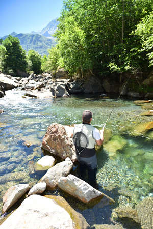 trout fishing: Fisherman trout fishing with bait in mountain river