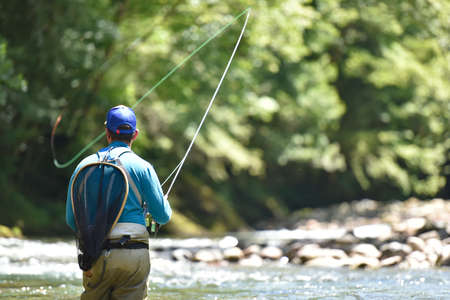 Flyfisherman vissen in de rivier berg Stockfoto