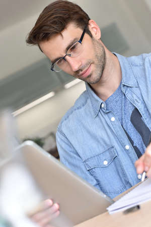 man at home working on digital tablet Stock Photo