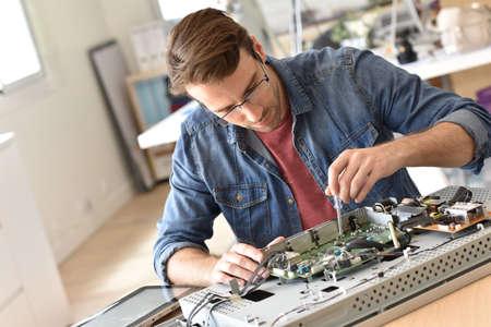 tv set: Repairman fixing tv set