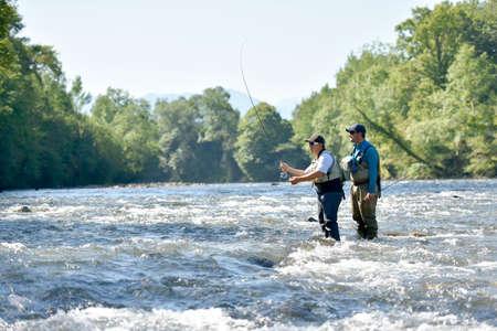 Flyfisherman met visgids in de rivier