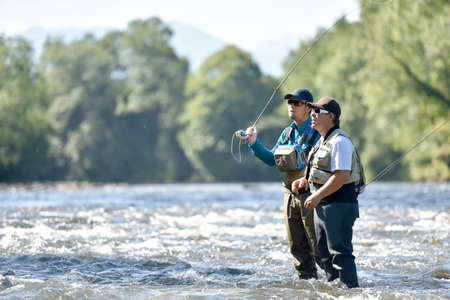 Flyfisherman with fishing guide in river Stock Photo