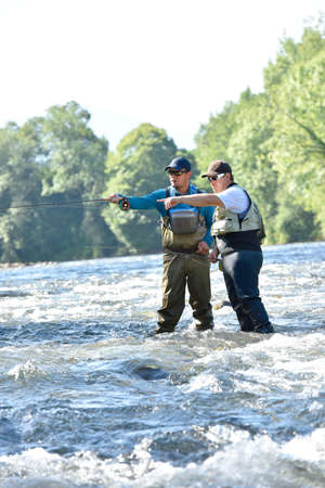 flyfishing: Flyfisherman with fishing guide in river Stock Photo