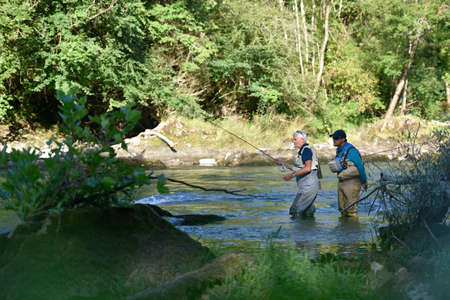 waders: Flyfisherman with fishing guide in river Stock Photo