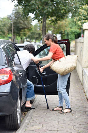 dependency: Young carer helping senior woman getting in car