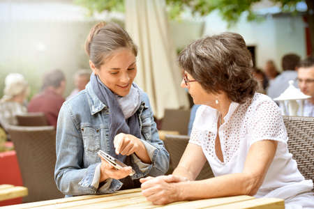 dependance: Senior woman and home carer at caf� terrace using smartphone Stock Photo