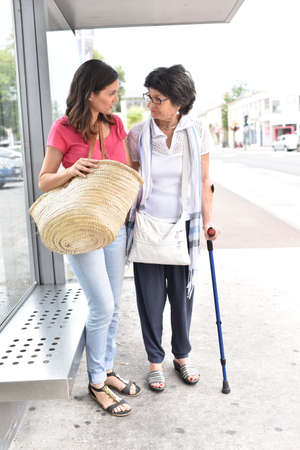 carer: Senior woman with home carer waiting for the bus